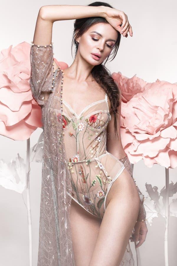 有经典构成和发型的美丽的女孩在有大花的精美内衣在背景 秀丽表面 免版税库存图片