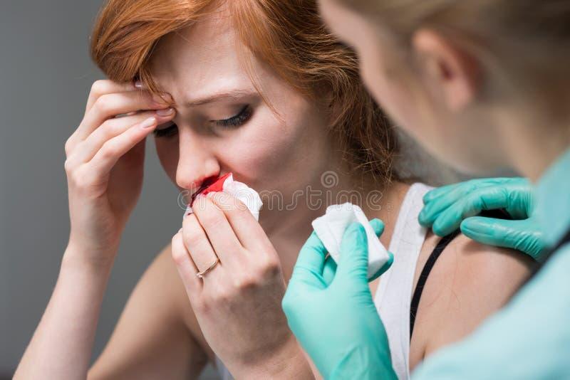 有鼻出血的妇女和护士 免版税库存照片