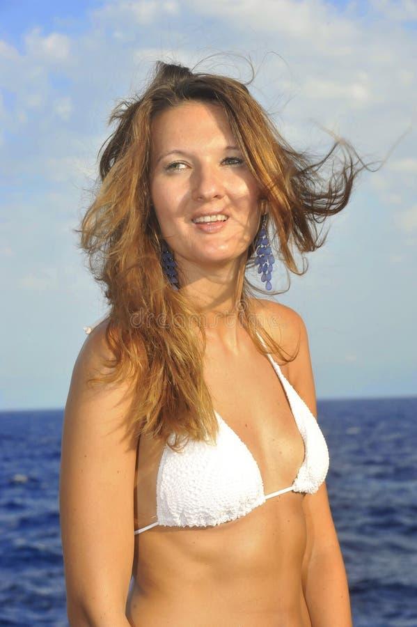有移动与风的头发的可爱的妇女站立在白色比基尼泳装微笑的海滩愉快 库存图片