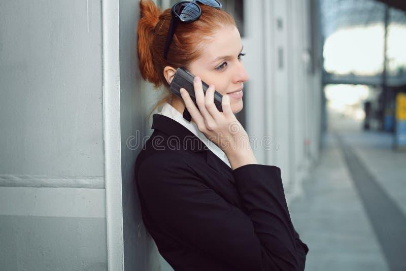有移动电话的女实业家 库存图片