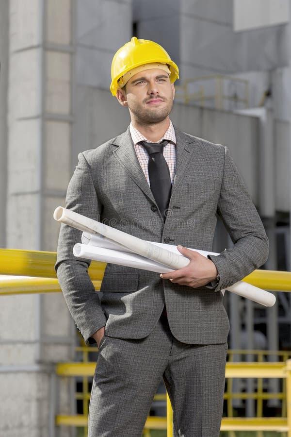 有滚动的年轻男性建筑师图纸在建造场所 免版税图库摄影