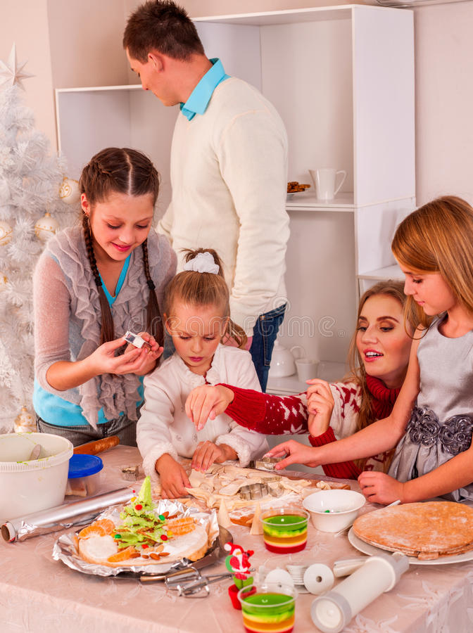 有滚动面团的孩子的家庭在Xmas厨房里 库存照片