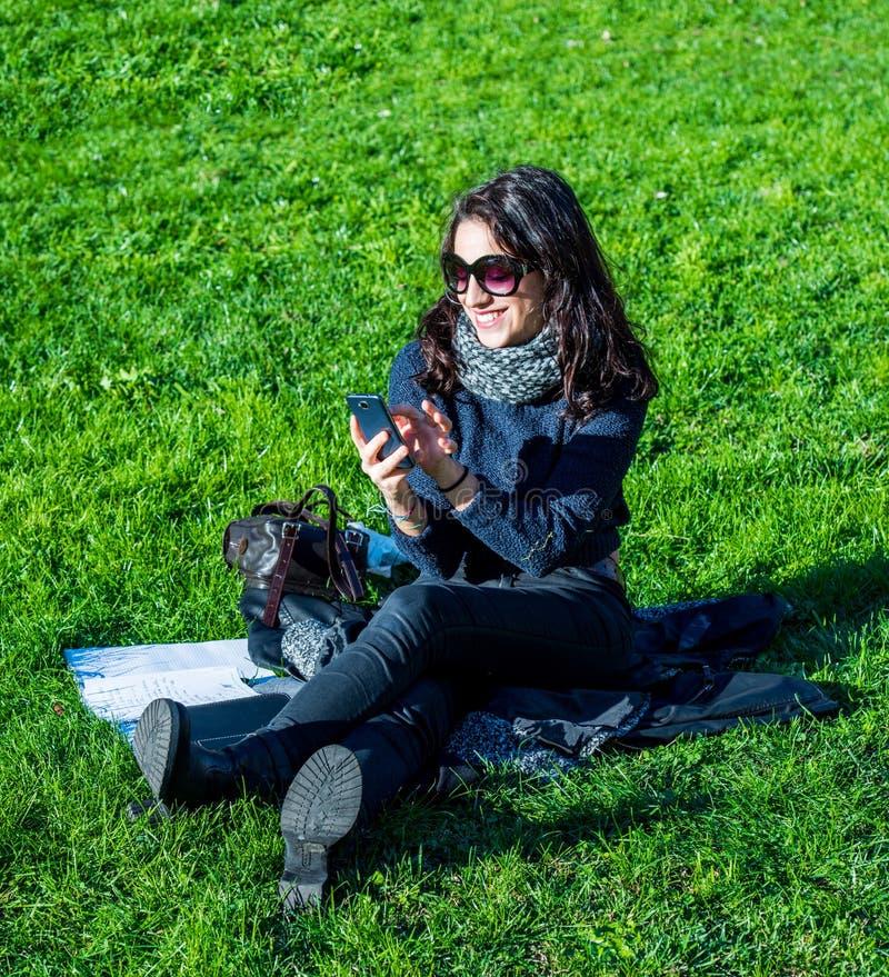 有黑发和太阳镜的美丽的十几岁的女孩写在她的电话的 免版税库存图片
