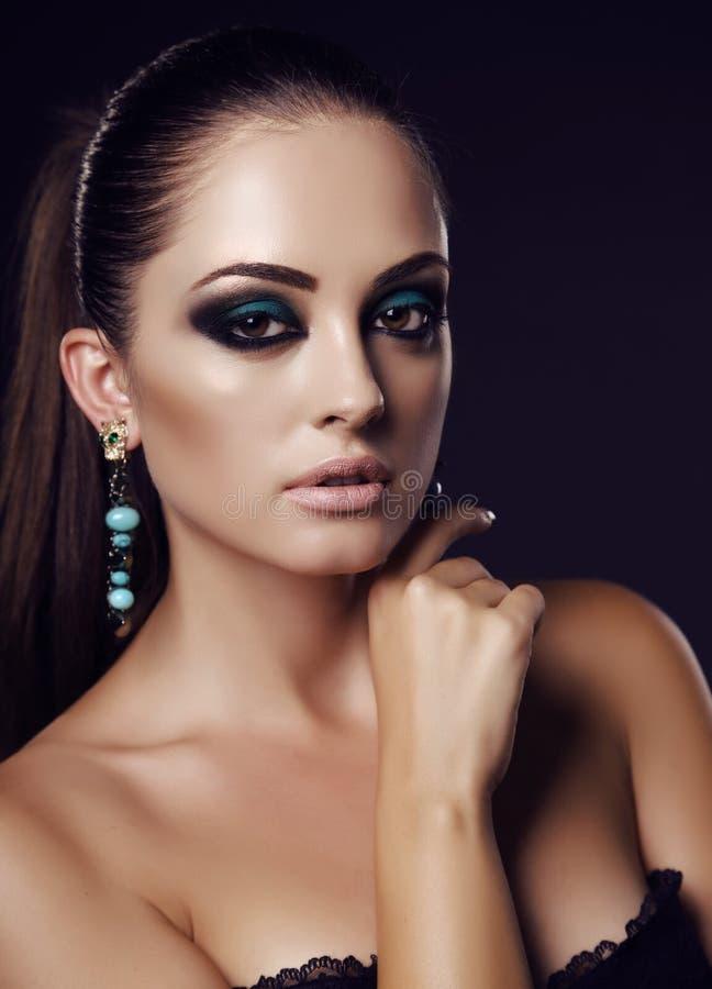 有黑发和晚上构成的性感的女孩与珠宝 免版税库存照片