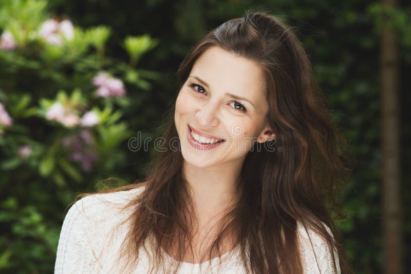 有黑发室外微笑的美丽的女孩 免版税库存照片