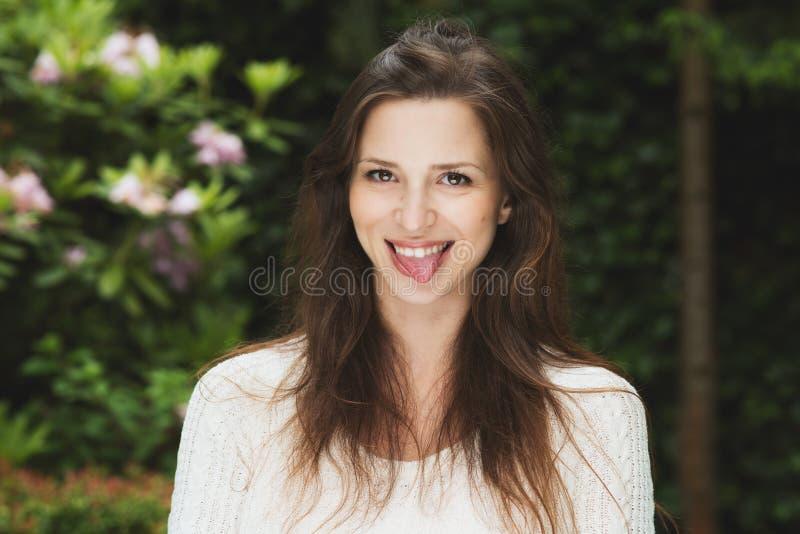 有黑发室外微笑的美丽的女孩 免版税库存图片