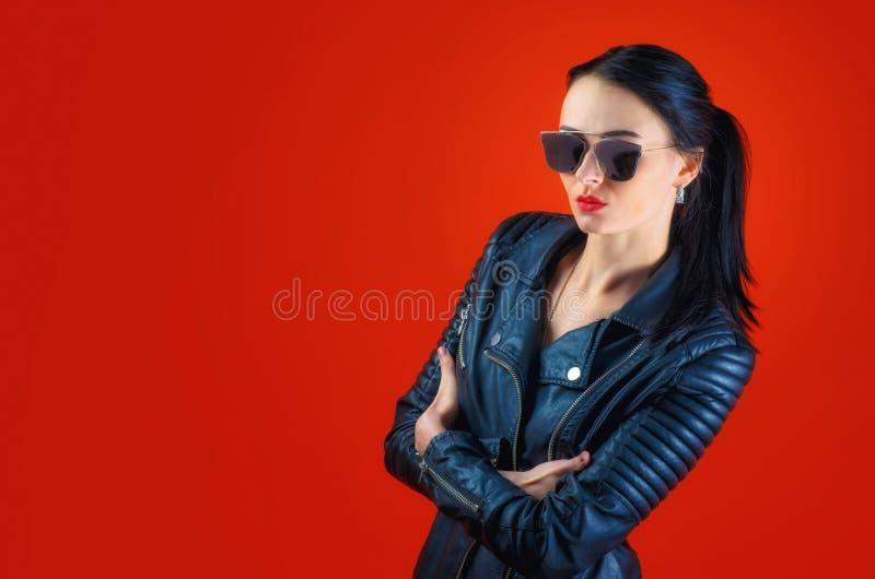 有黑发的严密的美丽的妇女在皮夹克 免版税库存图片