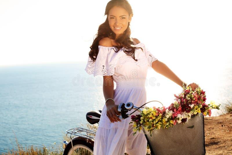 有黑发的俏丽的微笑的女孩在庄重装束坐自行车 免版税库存照片