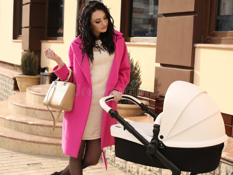 有黑发的华美的妇女走与婴儿车的 免版税库存图片