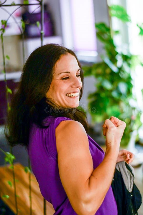 有黑发的女孩和紫罗兰穿戴显示她的肌肉和笑 免版税图库摄影
