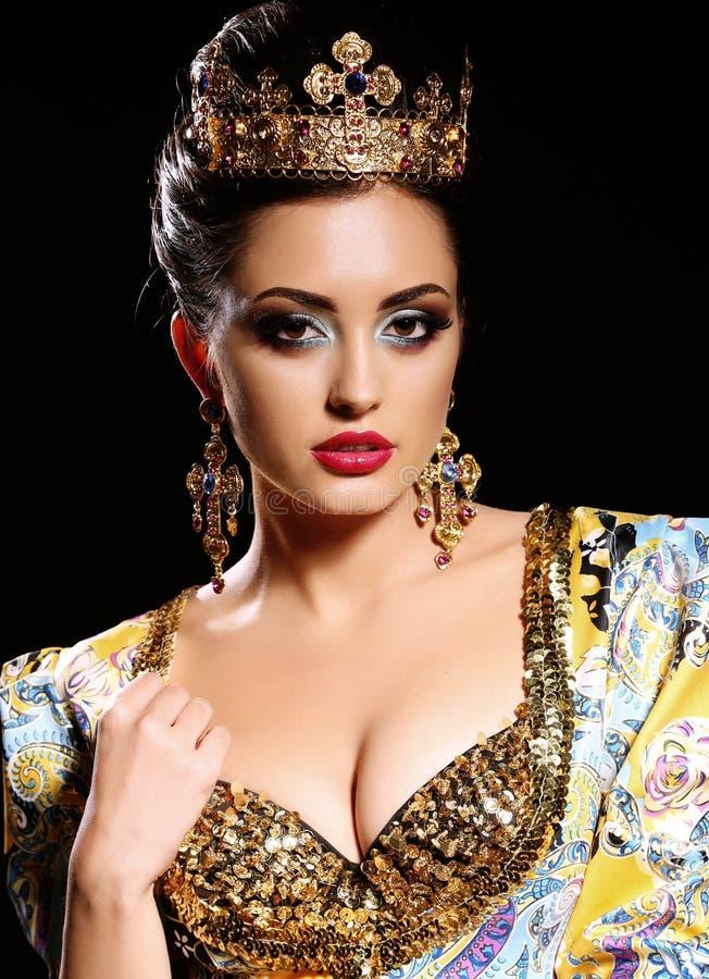 有黑发的妇女在有珠宝和冠的豪华金礼服, 库存图片