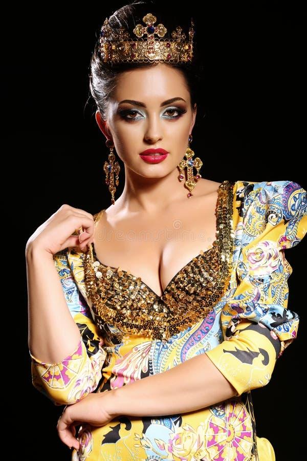 有黑发的妇女在有珠宝和冠的豪华金礼服, 免版税库存图片
