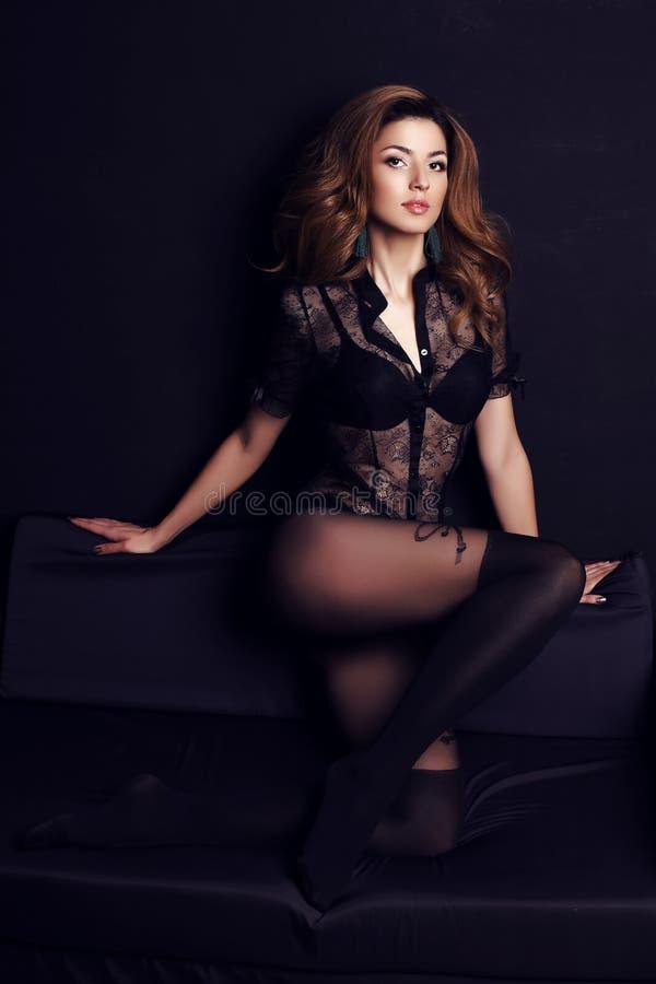 有黑发的妇女穿典雅的鞋带女衬衫和裤袜 免版税库存图片