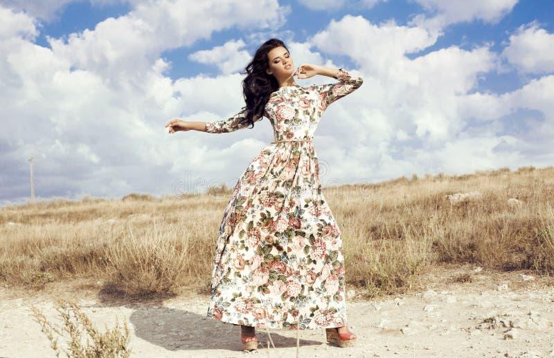 有黑发的妇女穿摆在夏天领域的豪华五颜六色的礼服 免版税库存照片