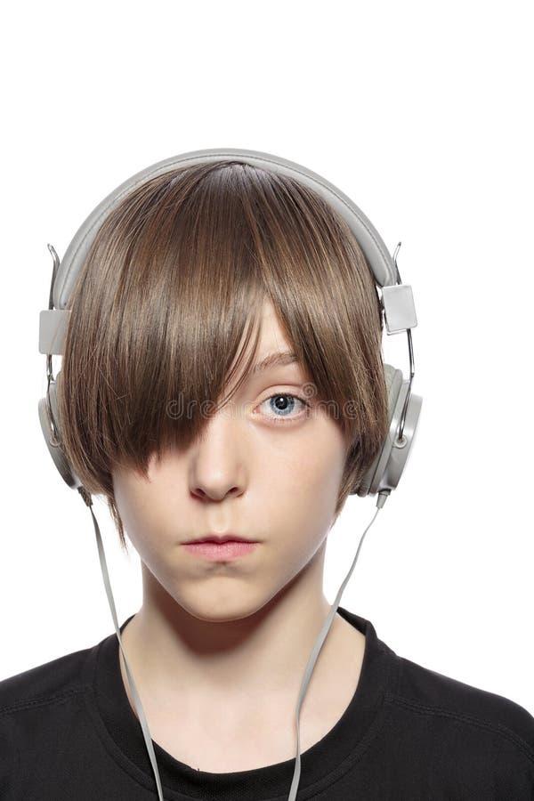 有头发的少年男孩一只眼睛和耳机 免版税库存照片