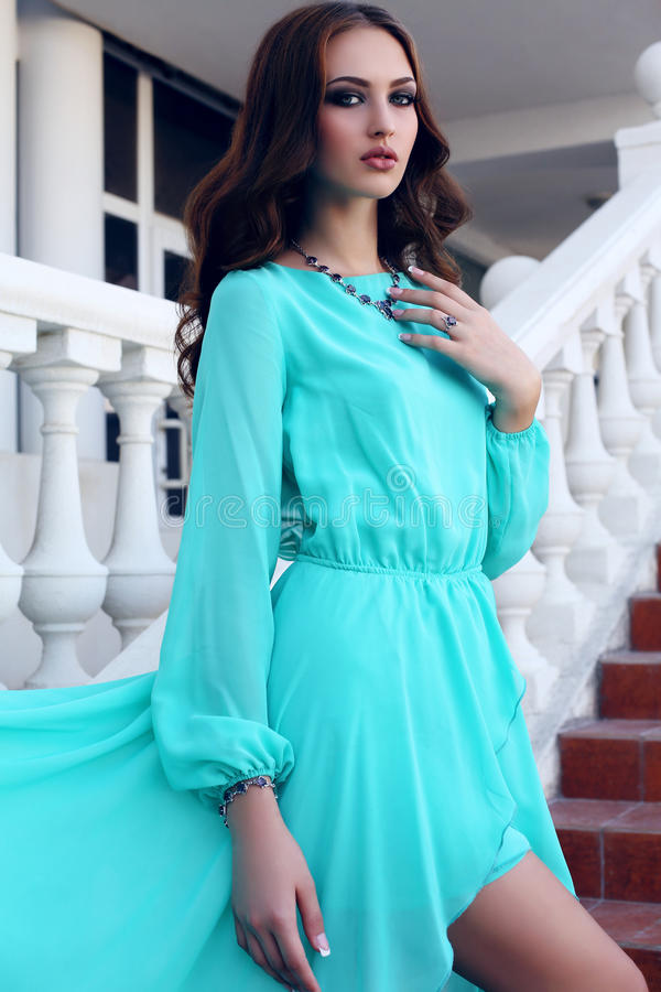 有黑发的美丽的女孩在摆在台阶的豪华蓝色礼服 库存照片