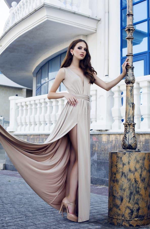 有黑发的美丽的妇女在典雅的米黄礼服 免版税库存照片