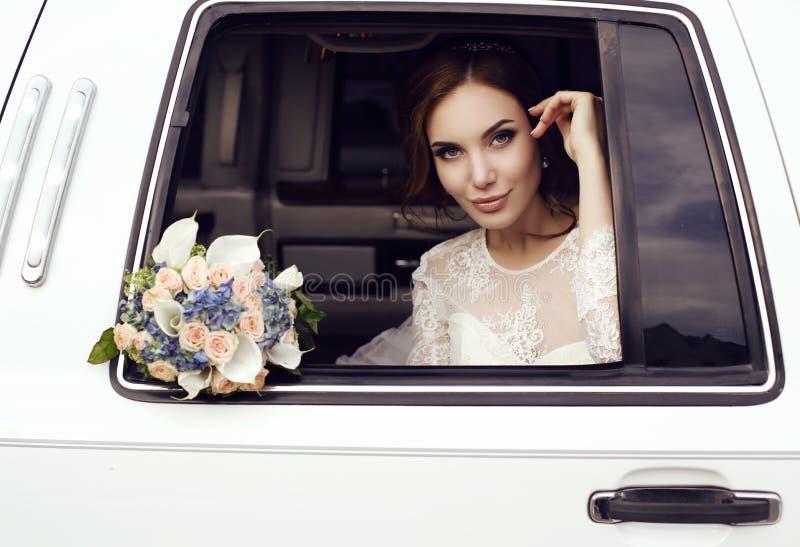 有黑发的肉欲的新娘在摆在汽车的豪华婚礼礼服 图库摄影