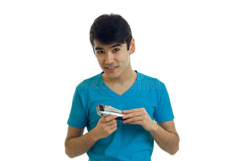 有黑发的英俊的年轻人是微笑和拿着飞剪机刮特写镜头 库存照片