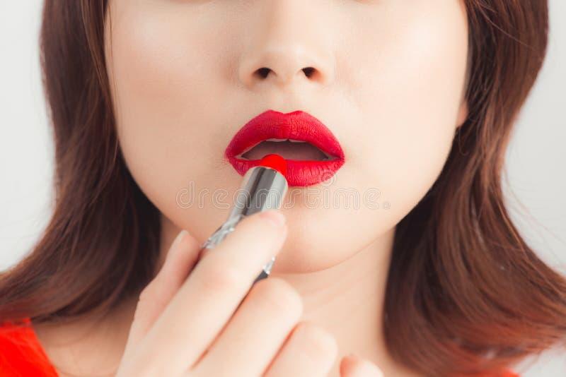 有黑发的年轻亚裔性感的妇女使用红色唇膏 图库摄影