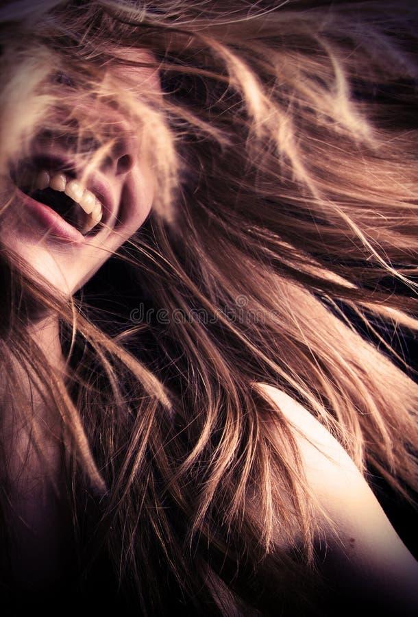 有头发飞行的Laughng青少年的女孩 库存照片