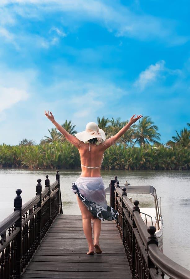 有从后面走看见的帽子的妇女在河跳船 免版税图库摄影