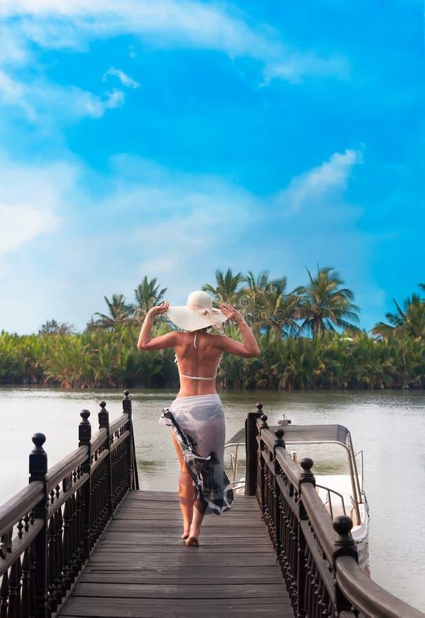 有从后面走看见的帽子的妇女在河跳船 免版税库存照片