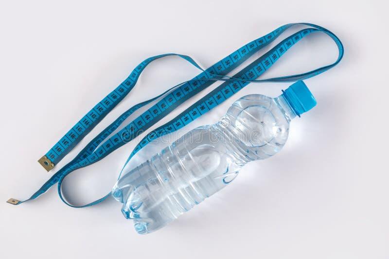 有水和措施磁带的瓶 库存照片