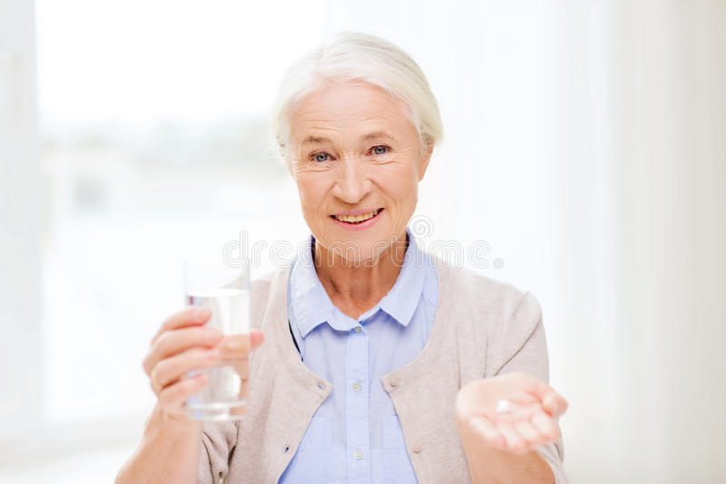 有水和医学的愉快的资深妇女在家 免版税库存照片