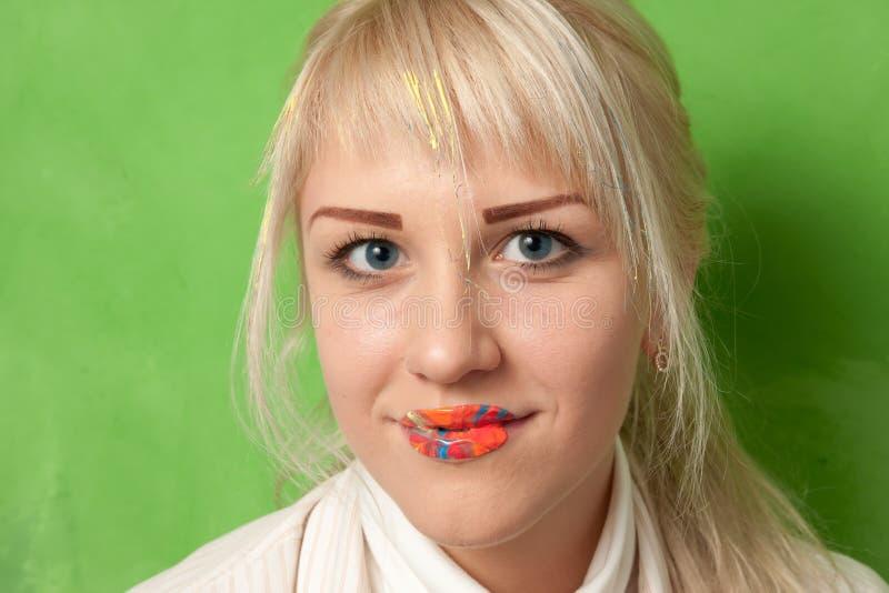 有嘴唇的可爱的微笑的女孩在明亮的油漆 图库摄影