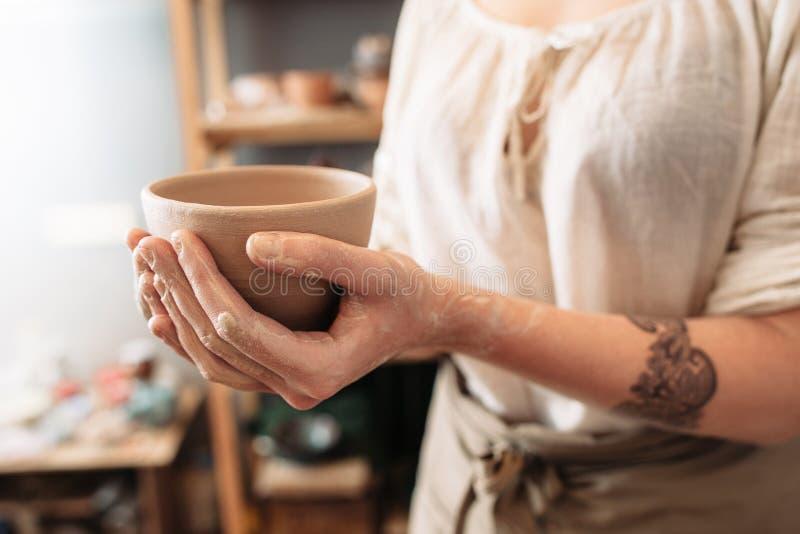 有黏土碗外形的女性陶瓷工手,特写镜头 免版税库存照片