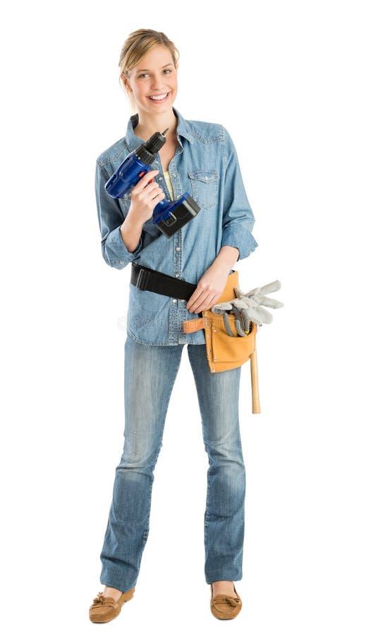 有钻子和工具传送带的愉快的女性建筑工人 免版税库存照片