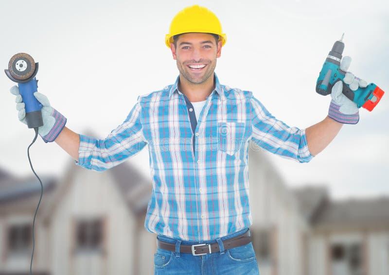 有钻子的建筑工人在建造场所前面 免版税图库摄影