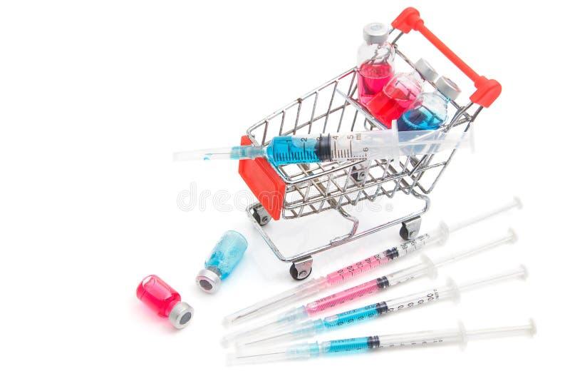 有医学小瓶和注射器的购物车 免版税库存照片
