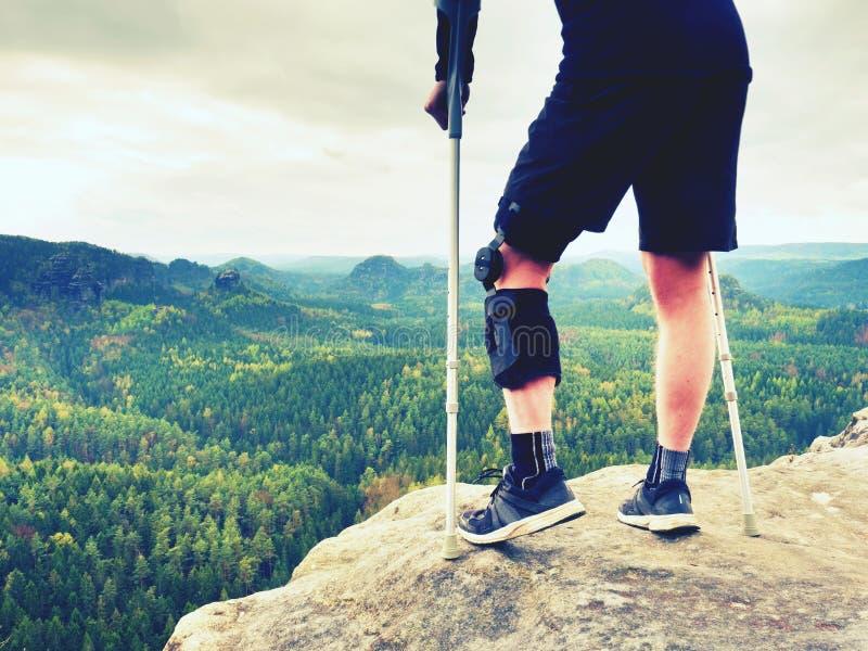 有医学拐杖的疲乏的创伤游人 有断腿的人在护膝垫以基于被暴露的岩石山顶为特色 图库摄影