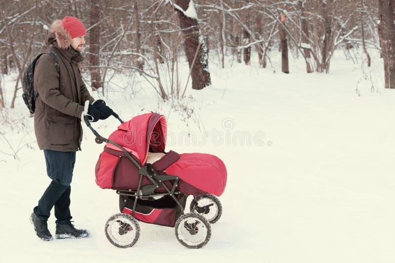 年轻有婴孩的人漫步的婴儿车在冬天公园 免版税图库摄影