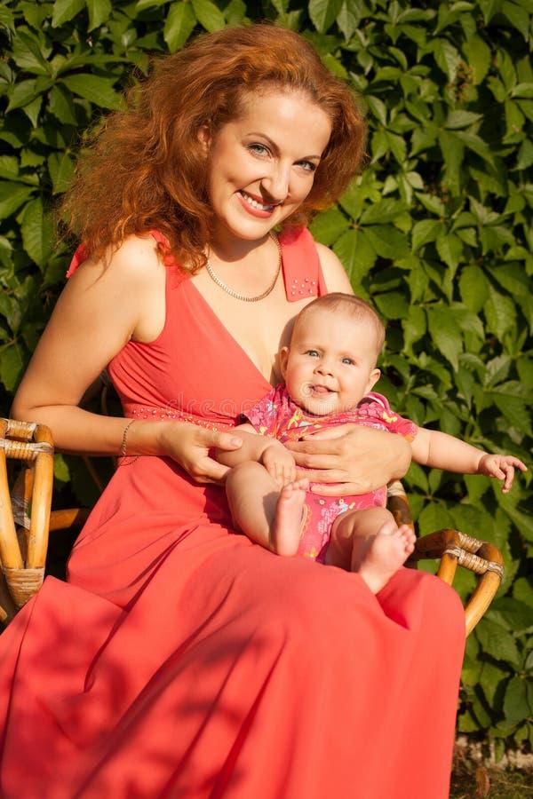 有婴孩的美丽的年轻母亲 库存图片