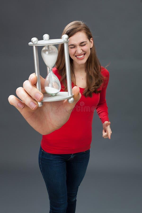 有1小时玻璃的兴奋的少妇在过大的手上 免版税库存图片