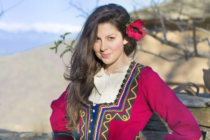 有巴尔干民间红色服装的美丽的年轻微笑的妇女 免版税图库摄影