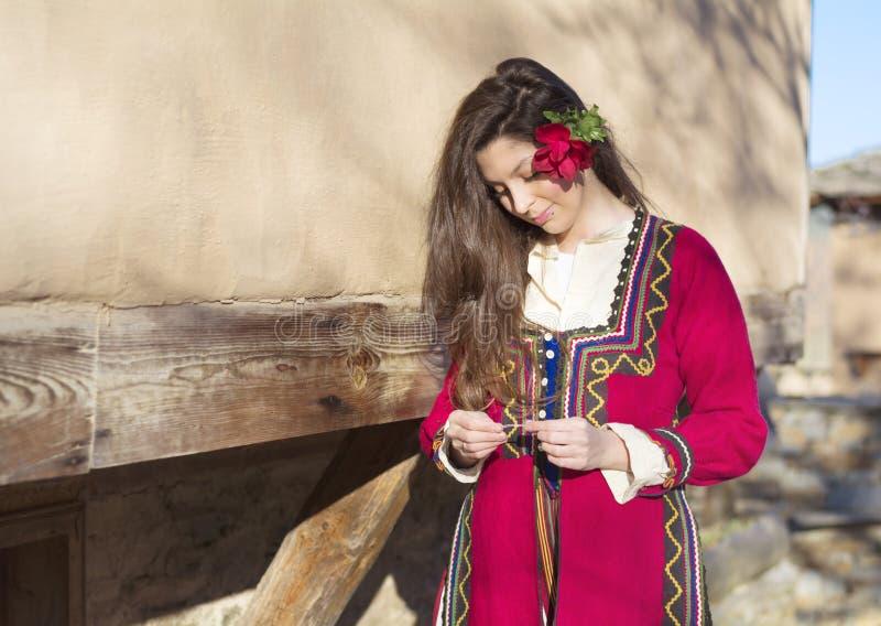 有巴尔干民间红色服装的美丽的年轻微笑的妇女 免版税库存图片