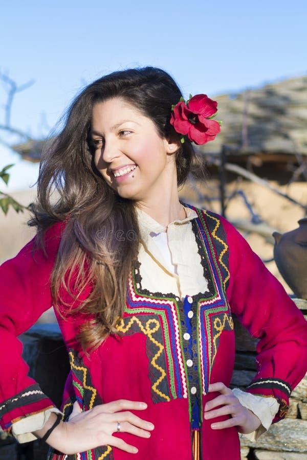 有巴尔干民间红色服装的美丽的年轻微笑的妇女 图库摄影