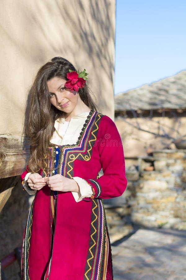 有巴尔干民间红色服装的美丽的年轻微笑的妇女 库存照片