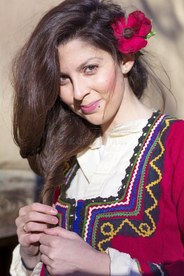 有巴尔干民间红色服装的美丽的年轻微笑的妇女 库存图片