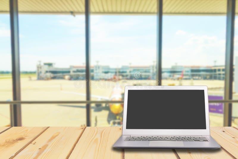 有黑屏的膝上型计算机在与机场的木桌上门ba的 免版税图库摄影