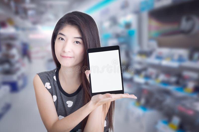 有黑屏的年轻亚洲妇女展示或显示片剂在嘘 免版税库存图片