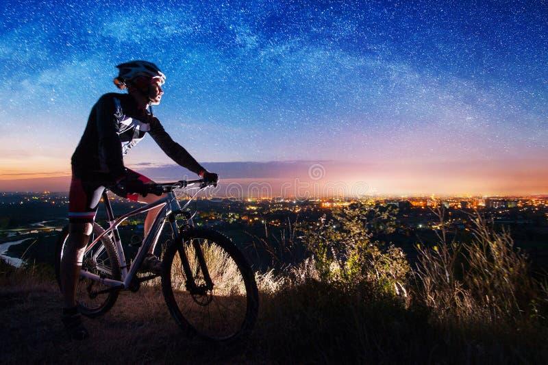 有登山车的自行车骑士在小山顶部 免版税库存图片