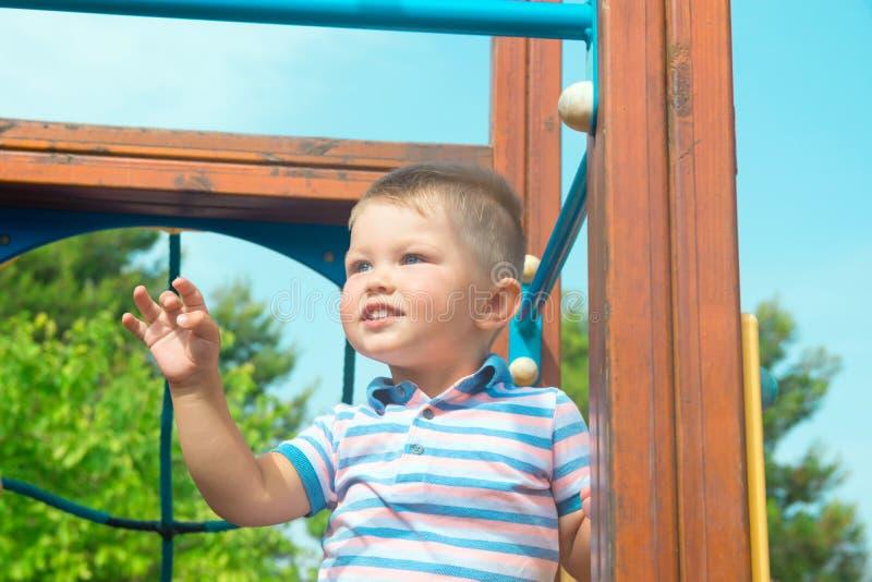 有2岁的蓝眼睛小孩的逗人喜爱的白种人白肤金发的男婴在城市公园微笑的操场站立 生动的明亮的夏天 图库摄影