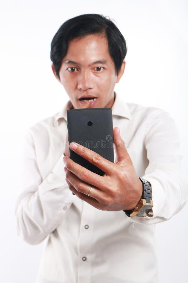 有他巧妙的电话的震惊亚裔人 图库摄影