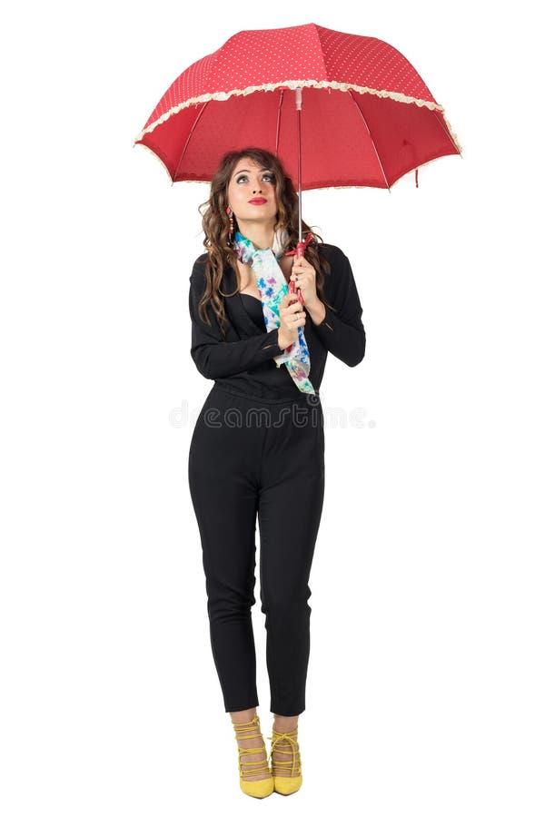 有围巾的逗人喜爱的时髦的女人在伞下期待雨的查寻 免版税库存照片