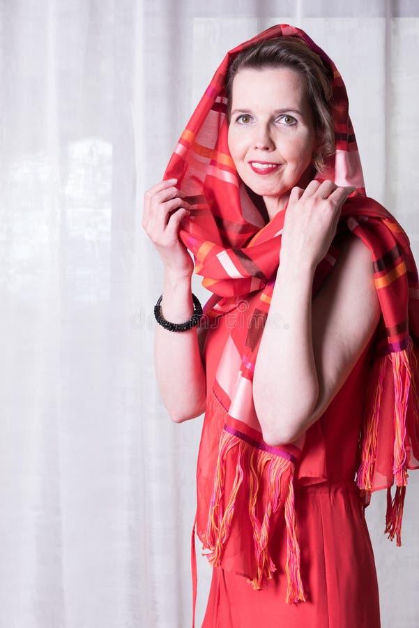 有围巾的画象可爱的妇女在她的头附近 库存照片